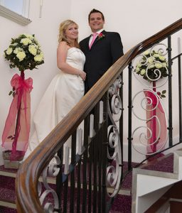 Bride and groom photographed on the grand staircase at the John Godber Centre